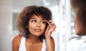 A woman checking her eyes and makeup in a mirror before using Bruder eye-wellness products, compresses, and kits to help relieve dry eye