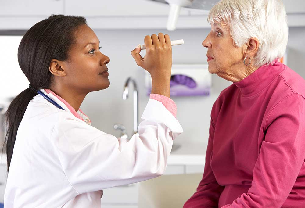 Elderly woman getting eyes examined by female doctor