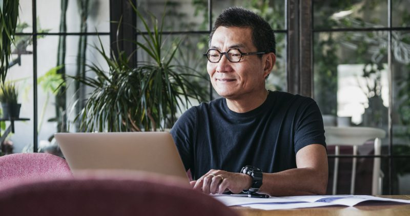 Smiling man working on laptop at home