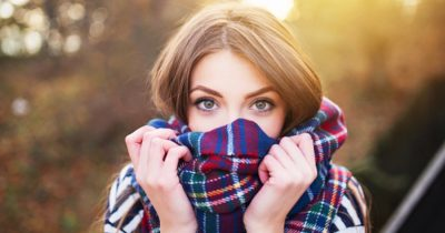 Girl experiencing fall allergy issues peeking over scarf at camera