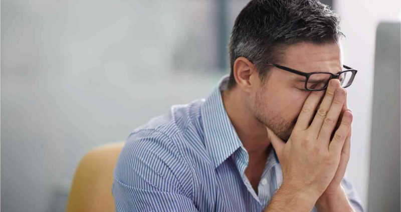 Man with glasses rubbing his blurry eyes
