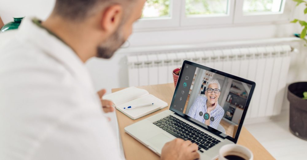 Doctor from a medical clinic  is having a video meeting with his senior patient.